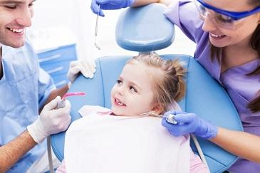Young girl sitting in dentist chair smiling l Pediatric Dentistry Madera CA