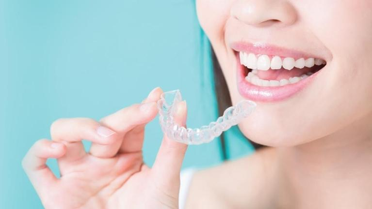 Woman putting in Invisalign clear aligner l Invisible Braces in Madera CA
